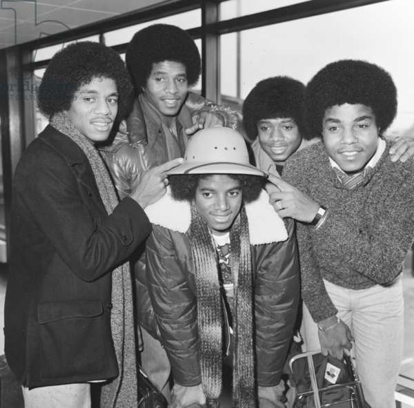 Members of The Jackson Five pop group make their way through the arrivals hall as they arrive in London for a UK tour, Michael Jackson shows of his hat as brothers point, 
