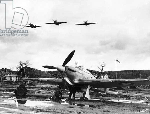 An RAF Hawker Hurricane sits on a muddy Russian airfield as Hurricanes fly overhead. WW2 1941 (b/w photo)