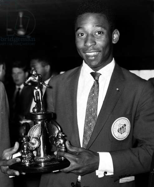 Brazilian football star Pele holding one of the team's trophies as Santos fly into London from HamburgOctober 1962 (photo)