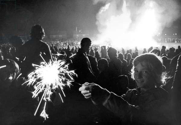 Sarah Stead, aged nine, of Preston Grange, North Shields, lights up the sky with a sparkler on bonfire night in November 1975 (b/w photo)