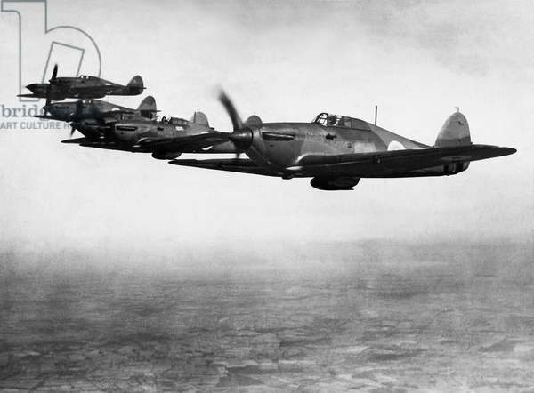 Six RAF early Hawker Hurricane MK1 fighter aircraft with two blade fixed pitch propellors in flight over England, c. August 1937 (b/w photo)