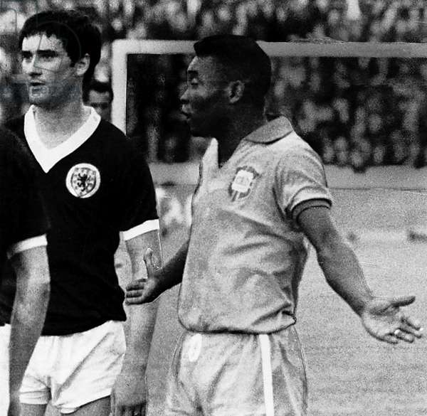 Pele stands next to Scotland player Jim Baxter protesting his innocence with his arms outstreched 1966Scotland V Brazil (photo)