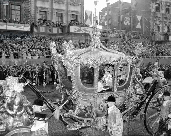 The Coronation of Queen Elizabeth II was the ceremony in which the newly ascended monarch, Elizabeth II, was crowned Queen of the United Kingdom, Canada, Australia, New Zealand, South Africa, Ceylon, and Pakistan, as well as taking on the role of Head of the Commonwealth. (Picture) Holding the Orb, smiling Queen leaves Westminster Abbey in state coach. 2nd June 1953 (b/w photo)
