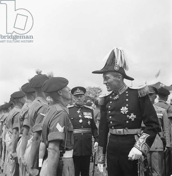 The new Governor of Kenya, Sir Evelyn Baring, in the full regalia of a Colonial Governor, inspects the Guard of Honour of the Lancashire Fusiliers before the opening ceremony of the New Session of the Kenya Legislative, 1952 (b/w photo)
