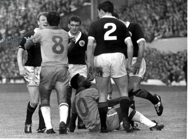 Brazilian football star Pele on a heap on the ground after clashing with Scotland's Billy Bremner in their international match at Hampden Park June 1966 (photo)