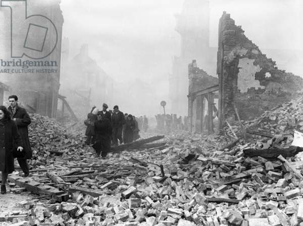 The city of Coventry shrouded in a cloak of smoke and drizzle as people wandered around in a daze taking in the destruction following the air raid of the 14th November 1940 (b/w photo)