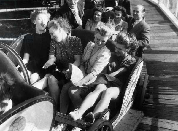 Four friends enjoy a fairground ride during the August bank holidays, 1946 (b/w photo)