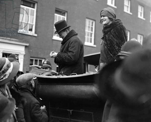 Winston Churchill is seen with his wife Clementine Churchill in an open topped car signing his autograph for the people of Epping. October 1924 (b/w photo)