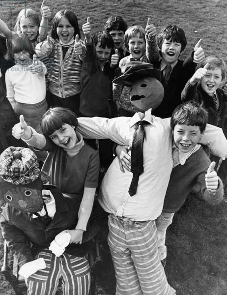 Rosalind Outy and Ian Mackenzie, both 10, pupils of Stokesley Junior School, get the thumbs up from their classmates for their own version of Guy Fawkes. 3rd November 1977 (b/w photo)