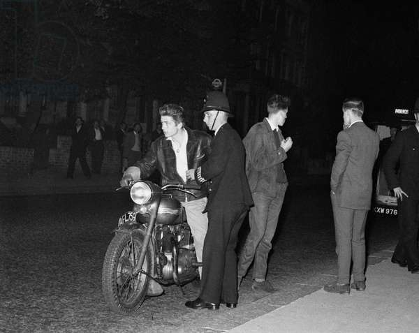 Police speaking to a youth on a motorcycle, Bramley Road, Notting Hill, 31st August 1958 (b/w photo)