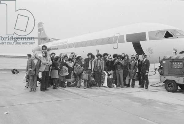 The Jackson Five pop group stand beside their plane as they arrive at London airport accompanied by members of their family and their crew, 7th November (b/w photo)