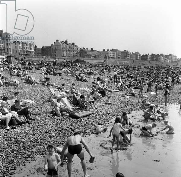 Crowded scenes on Brighton Beach as holidaymakers enjoy the hot summer weather, June 1960 (b/w photo)