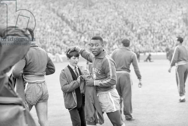 Scotland v Brazil International Friendly at Hampden Park, 25th June 1966. Pele gives a young autograph hunter a pat on the head. .. and his signature. Final score:Scotland 1-1 Brazil (photo)