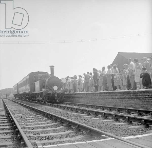 "Crowds on the platform at Horsted Keynes station await the arrival of the London, Brighton & South Coast Railway locomotive No. 55 ""Stepney"", a Bluebell Line train from Sheffield Park, 8th August 1960 (b/w photo)"