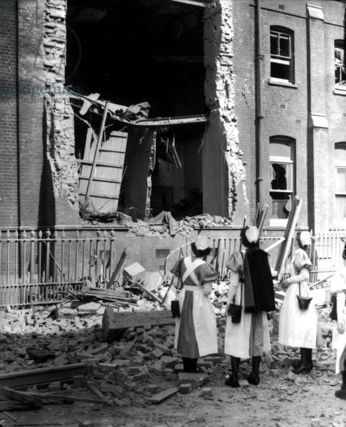 Nurses looking at a bombed hospital building during the Blitz (b/w photo)