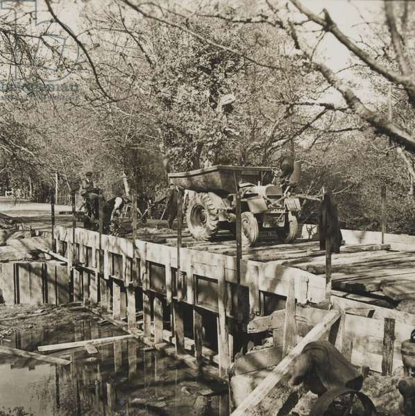 Britain's Second Front roads are widened: an old wooden bridge being replaced by a modern reinforced concrete one to carry the weight of heavier military traffic who will use it for the Second Front, April 1944 (b/w photo)