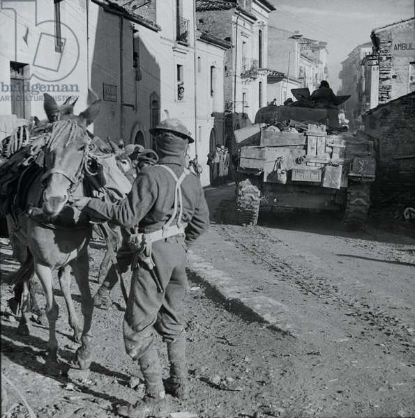 Indian soldier with a pack mule on the main street of Torine di Sangro, Italy, 1943 (lantern slide)