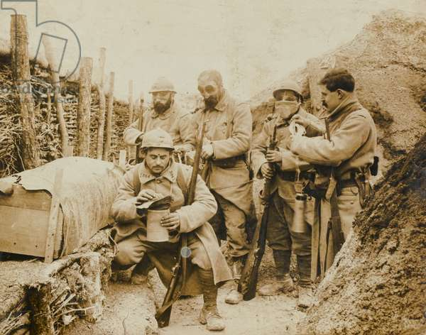 French troops don their gas masks while manning a trench on the Western Front, 1915 circa (b/w photo)