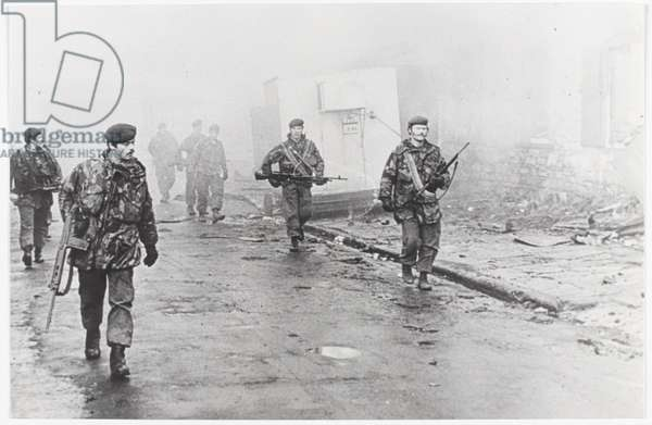 A view of a group of paras on foot patrol down a ruined street on the Falklands, 1982 (b/w photo)