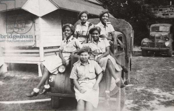 Five members of the West Indies Auxiliary Territorial Service sitting on a military vehicle, 1943-47 (b/w photo)
