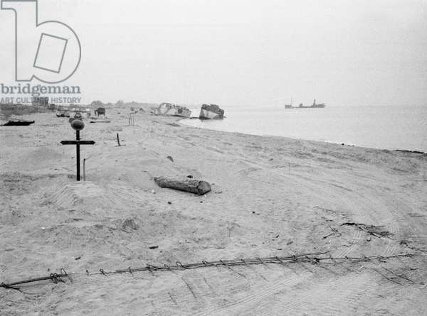 The disused beaches at Ouistreham with damaged craft wrecked on D-Day and the grave of an English sailor, from an album containing 210 photos compiled by Major W.H.J. Sale, 1944 (b/w photo)