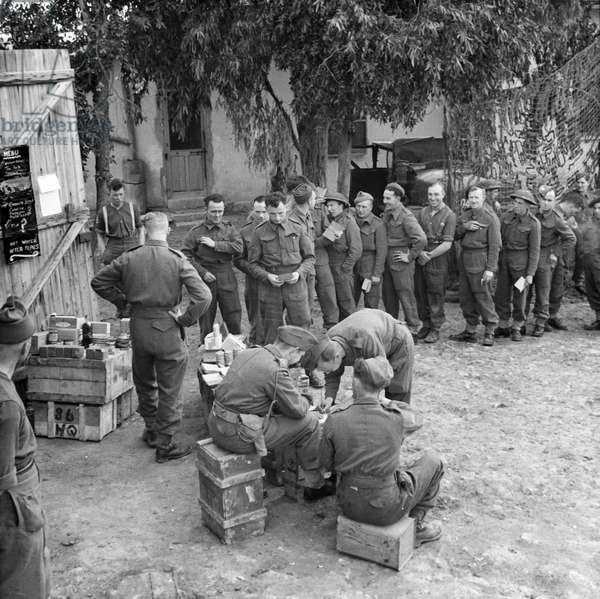 Troops from 78th Division lining up to collect their weekly ration from the NAAFI, March 1943 (lantern slide)