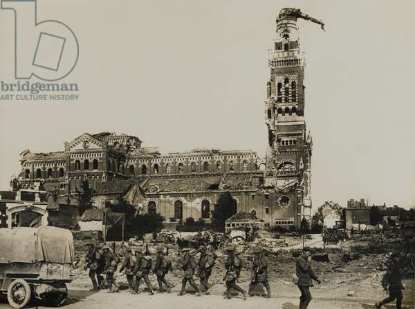 Soldiers marching past the ruined Basilica of Notre-Dame de Brebieres, Albert, with the Golden Virgin or Leaning Virgin on top of its tower, 1917-18 (b/w photo)