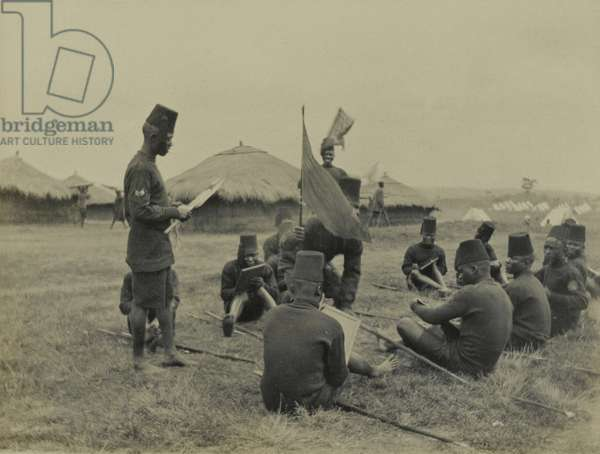 King's African Rifles soldiers undergo instruction in the use of signalling flags, 1916 circa (b/w photo)