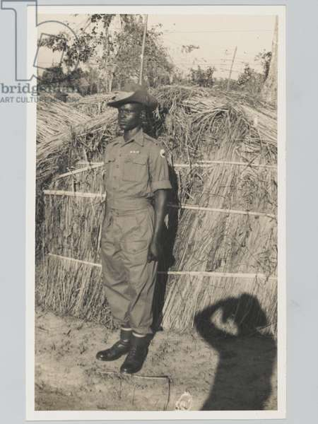 A soldier of the 4th (Uganda) Battalion, The King's African Rifles, awaits inspection, 1945 circa (b/w photo)