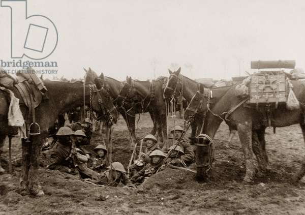 Cavalrymen resting in a shell hole (b/w photo)
