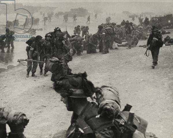 Soldiers wading ashore from landing craft at Ouistreham or Bernieres, St Aubin sector, 6th June 1944 (b/w photo)