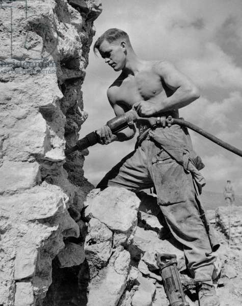 Driver E.A. Williams at work with a compressed air drill, Italy, c.1943-45, from a collection of 650 photographs compiled by the Commando Association (b/w photo)