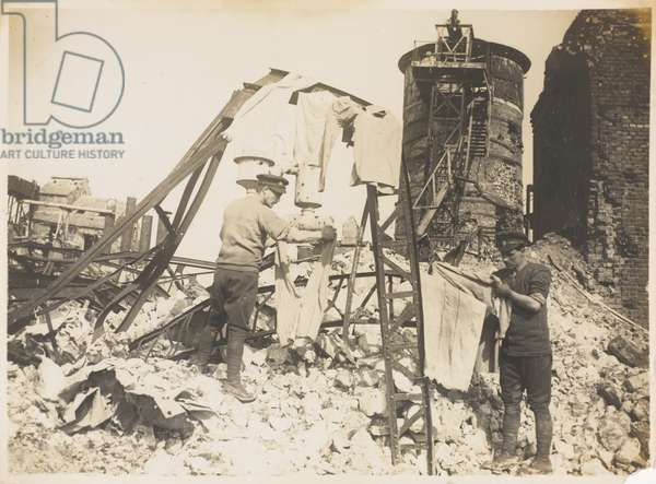 Troops billeted in a wrecked factory hanging out their washing, Bapaume, 8 March 1918 (b/w photo)