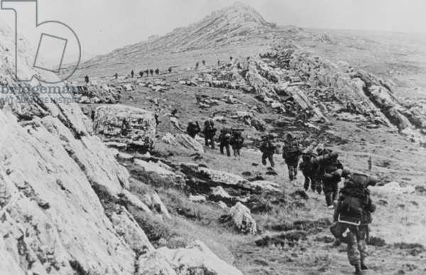 Yomping, a line of British troops winding up a rocky hillside, Falklands, 1982 (b/w photo)