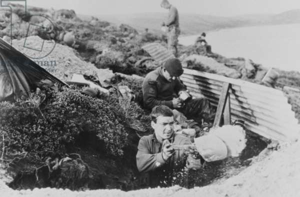 British troops, possibly Royal Marine Commandos, digging out a dugout overlooking a body of water, Falklands, 1982 (b/w photo)