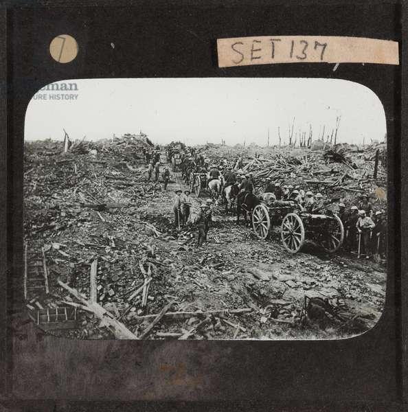 Horse-drawn ammunition limbers pass through the ruins of Longueval, September 1916 (lantern slide)