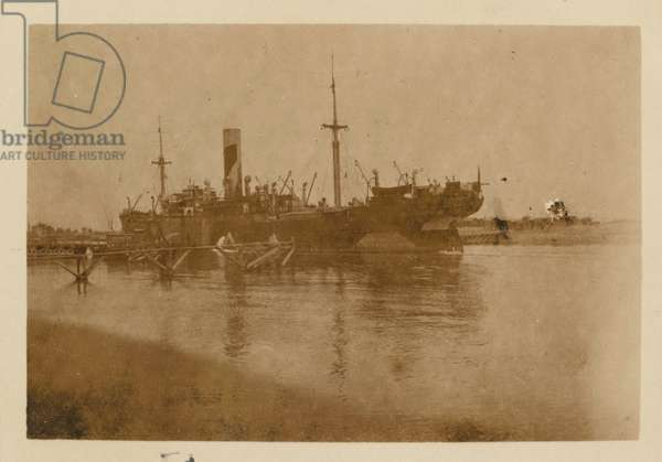 A Clan Line cargo ship painted with dazzle camouflage passing through the Suez Canal near Kantara, Egypt, 1916   (b/w photo)