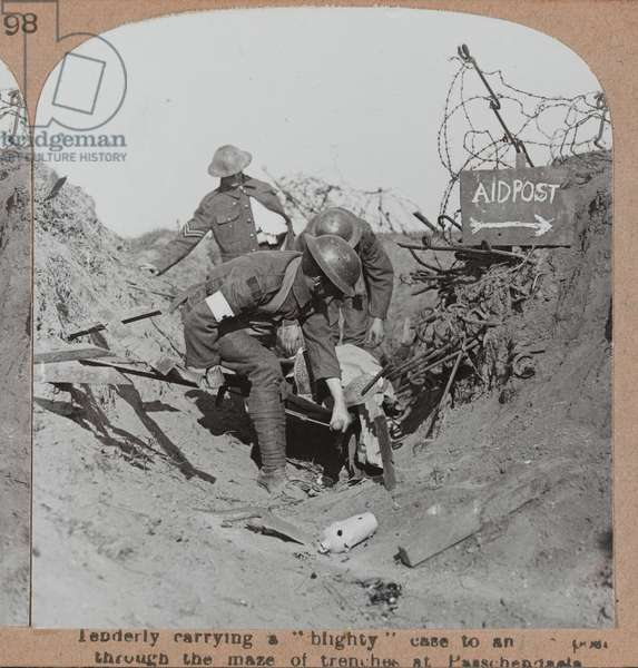 "'Tenderly carrying a ""blighty"" case to an aidpost through the maze of trenches at Passchendale', 1917 circa (b/w photo)"
