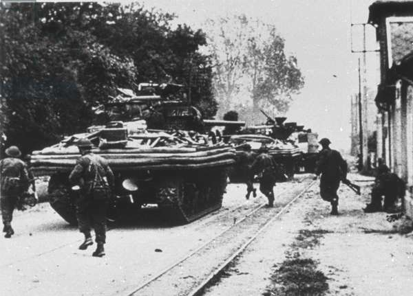 Amphibious tanks moving through a town, June 1944 (b/w photo)