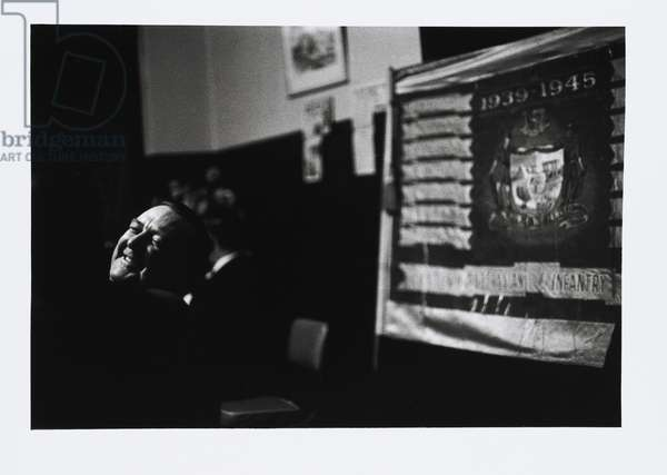 Smiling veteran before 1939-1945 Flag, Anzac Eve Reunion, Adelaide, 1963 (gelatin silver photo)