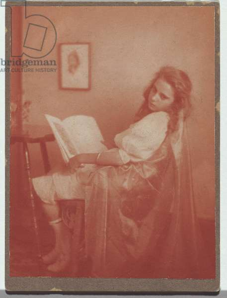 Young woman sitting in a chair holding an open book, c,1908 (red-toned gelatin paper print)