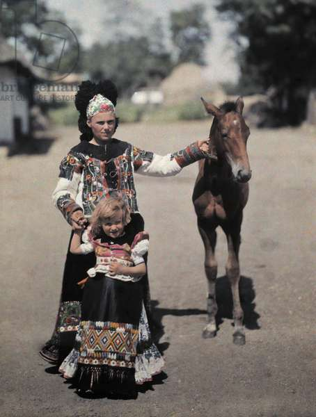 A mother and child, both in black, lead a colt down a lane, Mezokovesd, Hungary (autochrome)