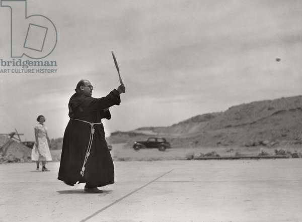 A priest playing tennis in his clerical robes, Caballo Dam, New Mexico, 1938
