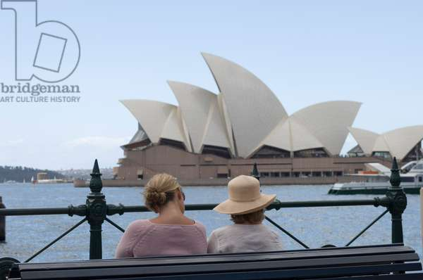 Two women resting on a bench across the harbor from the Sydney Opera House (photo)
