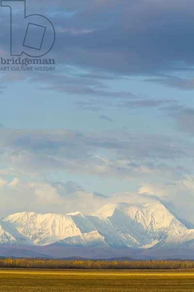 Cumulus clouds in blue sky above the snowy Alaska Range (photo)