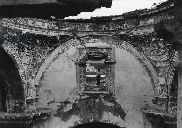 A boy framed in the window of a cathedral ruined in an earthquake, Antigua, Guatemala, 1936 (b/w photo)