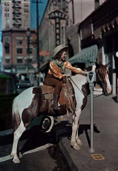 A cowgirl parks her horse at a meter in downtown El Paso, El Paso, Texas, USA, 1939 (photo)