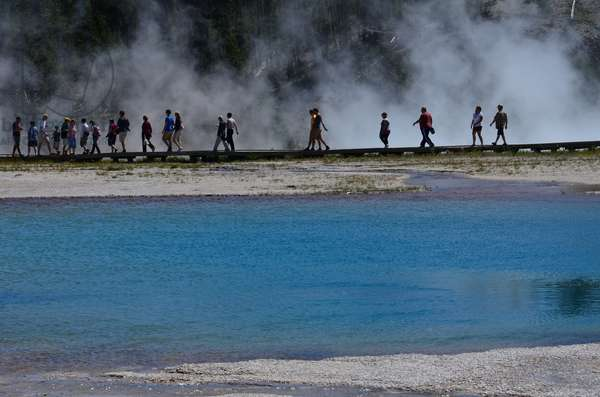 People walk on a boardwalk at the Prismatic Spring a colourful pattern of water and algae in Yellowstone National Park, Wyoming (photo)