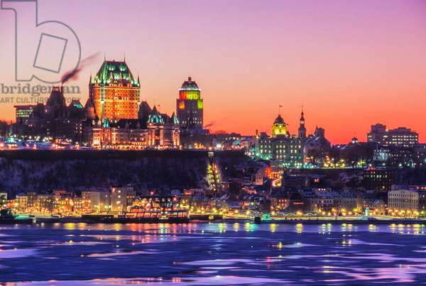 The iconic Chateau Frontenac dominates the skyline of Quebec City as seen from the Saint Lawrence River at sunset