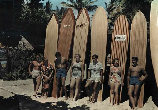 A group of surfers on Waikiki beach pose leaning against their boards, Oahu Island, Hawaii, 1937 (photo)